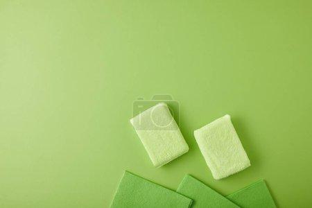 Photo pour Vue de dessus des éponges et chiffons pour le nettoyage de la maison sur vert - image libre de droit