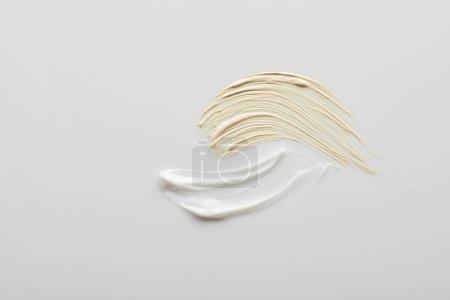 Foto de Vista superior de los cepillos de crema cosméticos y tonificantes sobre fondo gris. - Imagen libre de derechos