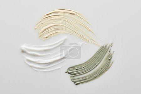 Photo pour Vue de dessus des coups de pinceau en argile, cosmétique et crème ton sur fond gris - image libre de droit