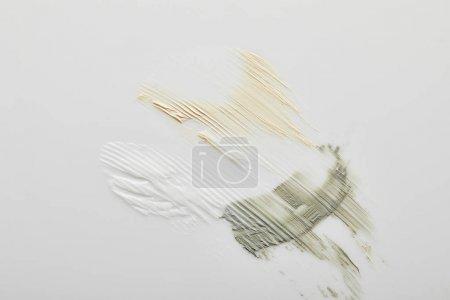 Foto de Vista superior de las pinceladas de barro, cosmético y crema de tono sobre fondo gris. - Imagen libre de derechos