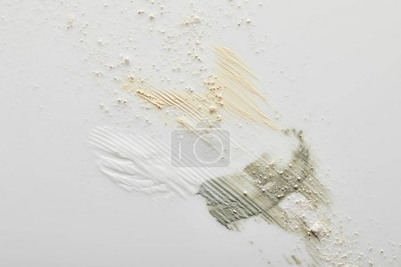Photo for Top view clay, cosmetic and tone cream brushstrokes on grey - Royalty Free Image