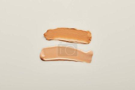 Foto de Vista superior de las pinceladas de crema de tono beige sobre fondo gris. - Imagen libre de derechos