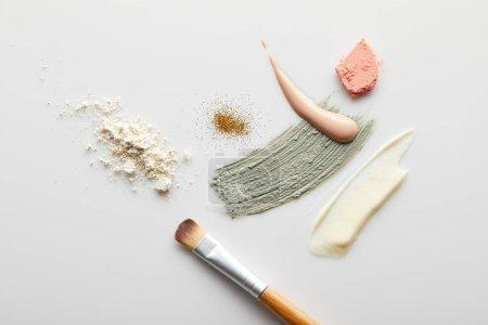 Photo pour Vue du dessus de la poudre pour le visage, de l'argile, de la crème cosmétique et tonique coups de pinceau, pinceau, blusher et étincelles dorées sur fond gris - image libre de droit