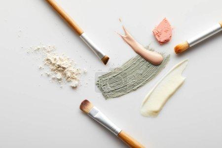 Photo pour Vue du dessus de la poudre pour le visage, de l'argile, des touches de crème cosmétique et tonique, des pinceaux et du blusher sur fond gris - image libre de droit