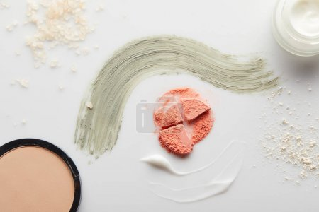 Top view of container with cosmetic cream and clay brushstrokes with blusher, face powder and sea salt on grey background
