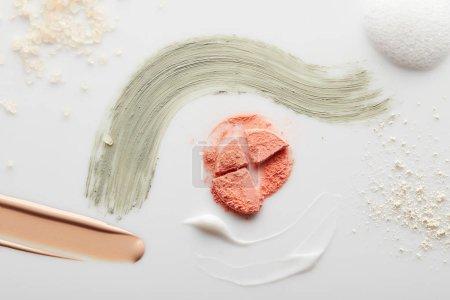 Foto de Vista superior de los pinceles cosméticos, tonificantes y arcillosos con blusher, polvo facial, sal marina y espuma de jabón en fondo gris. - Imagen libre de derechos