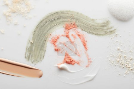 Photo for Top view of cosmetic, tone cream and clay brushstrokes with blusher, face powder, sea salt and soap foam on grey - Royalty Free Image