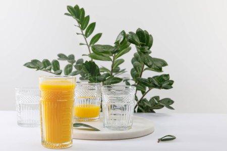 Photo pour Un verre de délicieux smoothie jaune sur une surface blanche près d'une plante verte isolée sur - image libre de droit