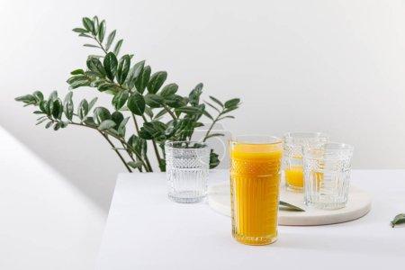 Photo pour Verre de délicieux smoothie jaune sur la surface blanche près de la plante verte - image libre de droit
