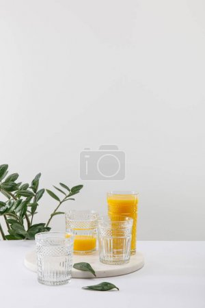 Photo for Glasses of delicious yellow smoothie on white surface near green plant isolated on grey - Royalty Free Image