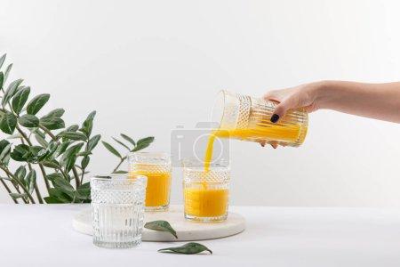 Photo pour Vue en coupe d'une femme versant un délicieux smoothie jaune en verre sur une surface blanche près d'une plante verte - image libre de droit