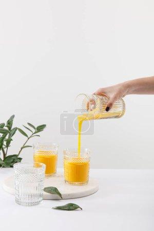 Photo pour Vue recadrée de la femme versant délicieux smoothie jaune dans le verre près de la plante verte isolée sur blanc - image libre de droit