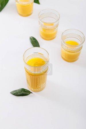 Photo pour Verres de délicieux smoothie jaune frais sur surface blanche avec feuilles vertes - image libre de droit