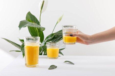 Photo pour Vue recadrée de la femme tenant verre de délicieux smoothie jaune frais près de vert plante de lis de paix sur fond blanc - image libre de droit