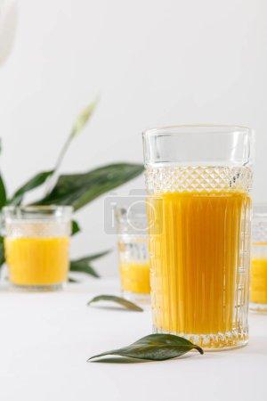 Photo pour Foyer sélectif de verre de délicieux smoothie jaune frais sur la surface blanche près de vert plante de lis de paix isolé sur gris - image libre de droit