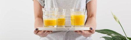 Photo pour Vue en coupe d'une femme tenant un plateau avec des verres de délicieux smoothie jaune frais près d'une plante de lis vert isolé sur une pellicule blanche panoramique - image libre de droit