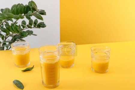 Photo for Glasses of fresh delicious yellow smoothie near green plant - Royalty Free Image