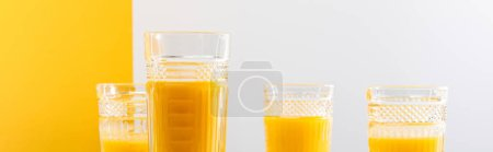 Photo for Glasses of fresh delicious yellow smoothie on grey and yellow background, panoramic shot - Royalty Free Image