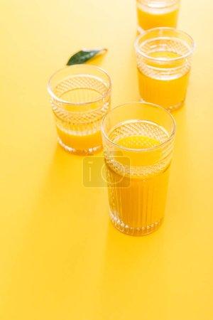 Photo pour Mise au point sélective des verres de délicieux smoothie jaune frais près de la feuille verte - image libre de droit