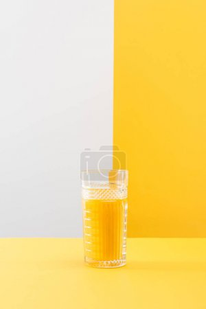 Photo for Glass of fresh delicious yellow smoothie on grey and yellow background - Royalty Free Image