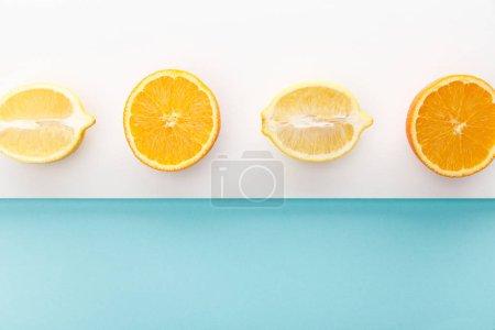 Photo pour Vue en haut des moitiés orange et citron sur fond bleu et blanc - image libre de droit