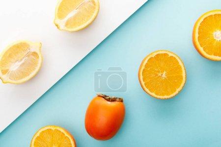 Photo pour Vue de dessus des moitiés orange et citron avec kaki sur fond bleu et blanc - image libre de droit