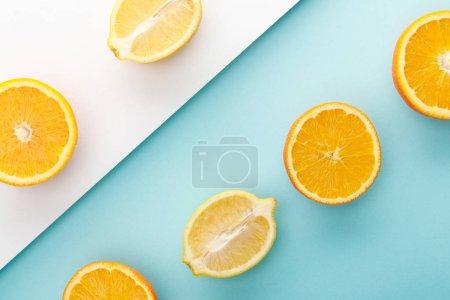 Photo pour Vue du haut des oranges coupées et des moitiés de citron sur fond bleu et blanc - image libre de droit