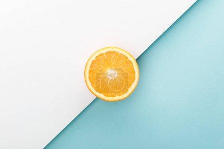 Photo pour Vue de dessus de la moitié orange sur blanc et bleu - image libre de droit