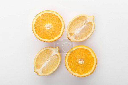 Photo pour Vue de dessus des moitiés orange et citron sur fond blanc - image libre de droit