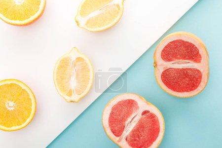 Photo pour Vue en haut des moitiés orange, citron, pamplemousse sur fond bleu et blanc - image libre de droit