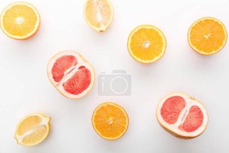 Foto de Vista superior de naranjas cortadas, limón, flores a la mitad sobre fondo blanco. - Imagen libre de derechos