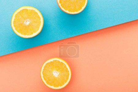 Photo pour Vue en haut des moitiés d'oranges sur fond bleu et orange - image libre de droit