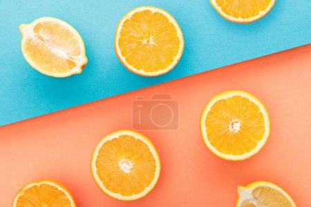 Photo for Top view of cut oranges and lemon halves on blue and orange background - Royalty Free Image