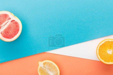 Photo pour Vue en haut des moitiés d'agrumes sur fond bleu, orange et blanc - image libre de droit