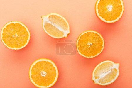 Top view of citrus fruits halves on orange background