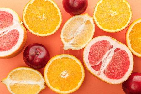 Photo pour Vue en haut des moitiés d'agrumes et des pommes sur fond orange - image libre de droit