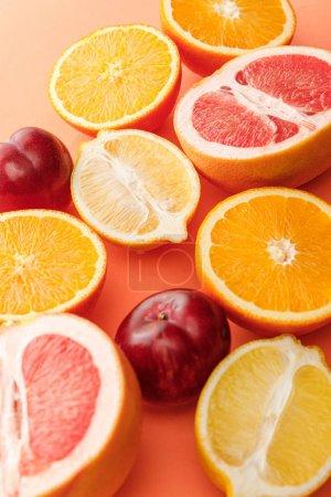Photo pour Orientation sélective des moitiés d'agrumes et des pommes sur fond orange - image libre de droit