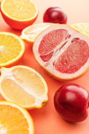 Photo pour Moitiés d'agrumes et pommes sur fond orange - image libre de droit