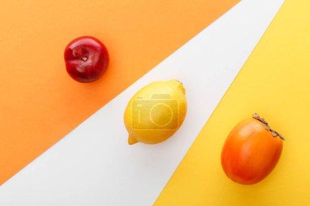 Foto de Vista superior de limón, persimón y manzana sobre fondo amarillo, naranja y blanco. - Imagen libre de derechos