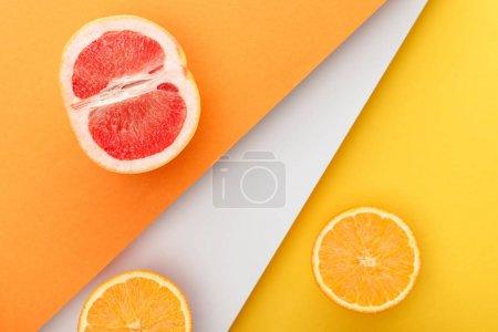 Photo pour Vue de dessus des moitiés d'agrumes sur fond jaune, orange et blanc - image libre de droit