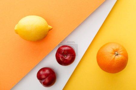 Foto de Vista superior de cítricos y manzanas sobre fondo amarillo, naranja y blanco. - Imagen libre de derechos