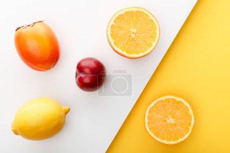 Photo pour Vue en haut des moitiés orange, du simmon, du citron et de la pomme sur fond jaune et blanc - image libre de droit
