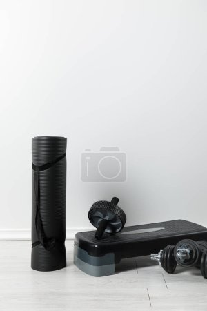 Photo for Black fitness mat and sports stuff on floor at home - Royalty Free Image