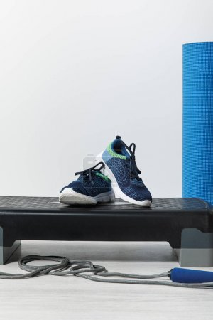Photo for Step platform, blue fitness mat, skipping rope and sneakers on floor at home - Royalty Free Image