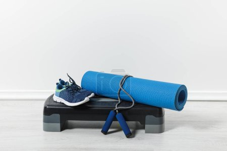 Photo for Step platform, fitness mat, jump rope and sport shoes on floor at home - Royalty Free Image