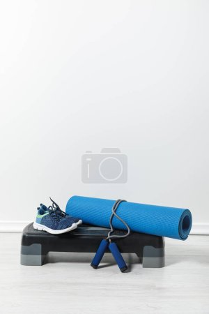 Photo for Step platform, fitness mat, skipping rope and sneakers at home - Royalty Free Image