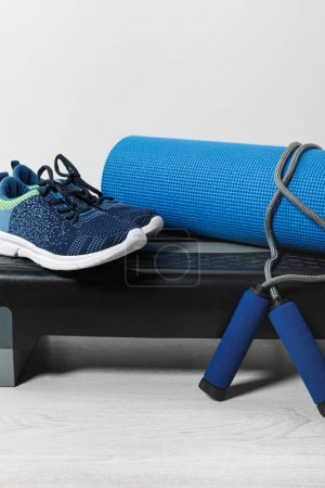 step platform, fitness mat, skipping rope and sneakers