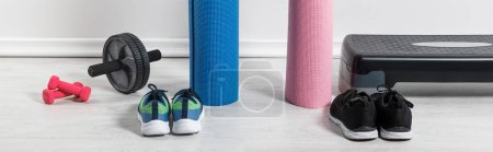 Photo for Panoramic shot of yoga mats, sneakers, step platform and sport equipment on floor at home - Royalty Free Image