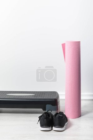 Photo for Step platform, pink fitness mat and sneakers on floor at home - Royalty Free Image