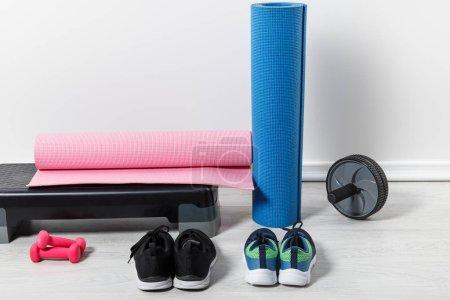 Photo pour Plateforme pas à pas, tapis de fitness et vêtements de sport sur le sol à la maison - image libre de droit
